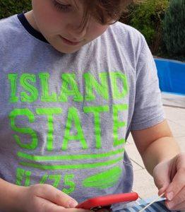 4.Sohn mit Makrolinse am Smartphone